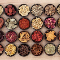 24961478 - large chinese herbal medicine selection in wooden bowls over papyrus background