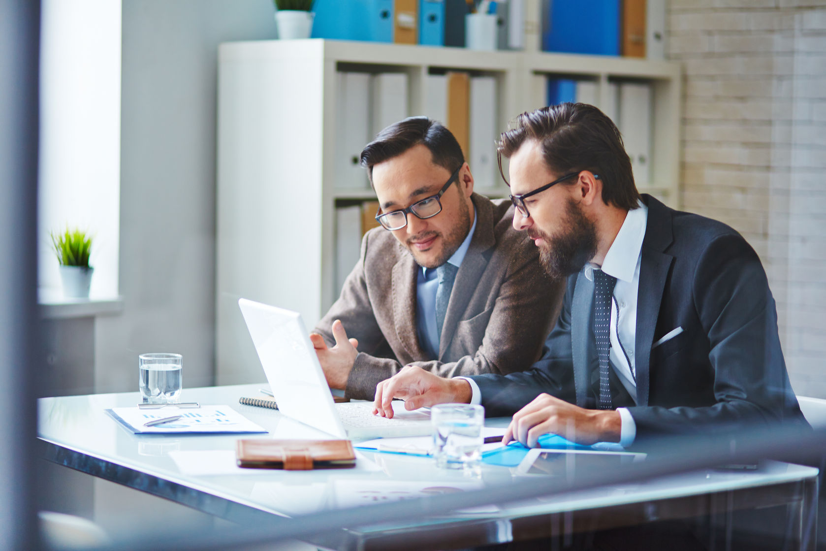 36271257 - young businessman with beard showing new project to his colleague in office